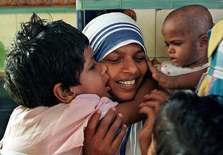 ONE OF EIGHT PHOTOS BY PHOTOGRAPHER JOHN MOORE-- Sister Leatrice smiles as she is is hugged and kissed by orphans under her care in the Shishu Bhavan orphanage in Calcutta, Thursday, Sept. 11, 1997. Most of the children from the home are placed in Indian families, others are adopted by Europeans. (AP Photo/John Moore)